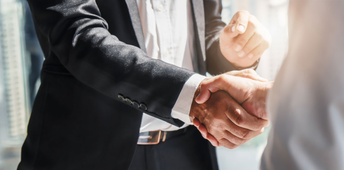 two business people in suite shaking hands