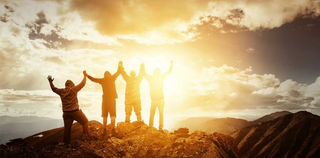 4 people at the top of the mountain during sunrise, with arms up and holding hands, celebrating